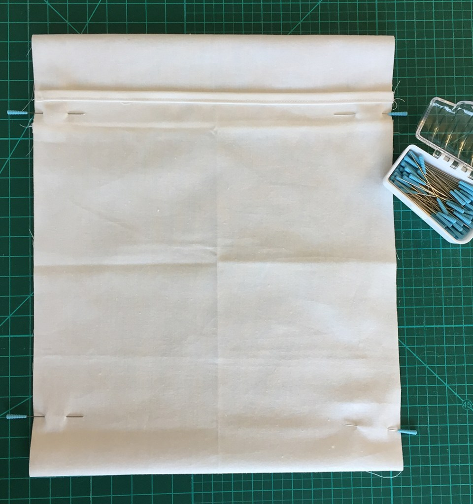 a fabric enveloped pinned along two sides ready to be sewn