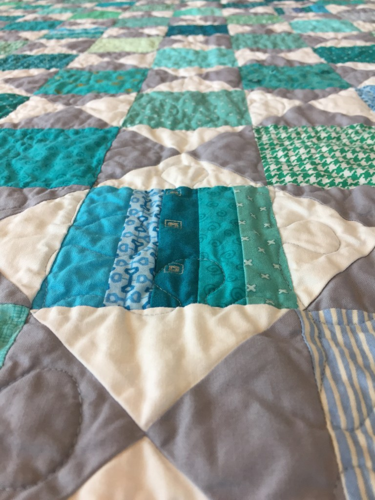 Close-up view of a finished quilt showing grey, white, and teal piecing and a puzzle piece quilting motif