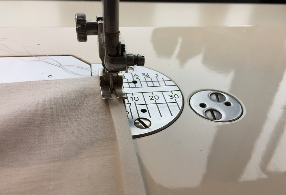 a sewing machine stitching down a double-folded hem along the edge of white fabric