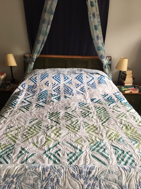 quilt with blue or green and white striped blocks draped over a bed