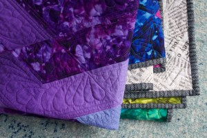 A folded quilt showing purple fabric, fabric that looks like newsprint, and a striped binding