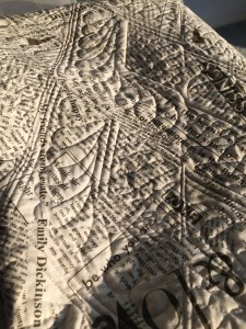The back of a quilt made from a newsprint-like print in strong sunlight