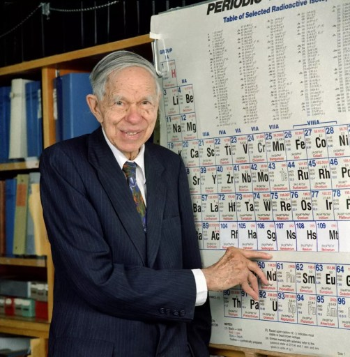 Glenn T. Seaborg señalando el elemento que lleva su nombre en una tabla periodica