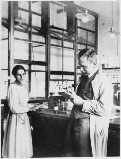 """Otto Hahn y Lise Meitner, 1913, en el laboratorio químico del Instituto Químico Kaiser Wilhelm. Cuando un colega que ella no reconoció dijo que se habían conocido antes, Meitner respondió: """"Probablemente me confundes con el profesor Hahn."""