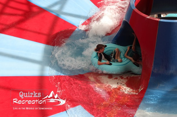 Two boys riding a tube on a water slide