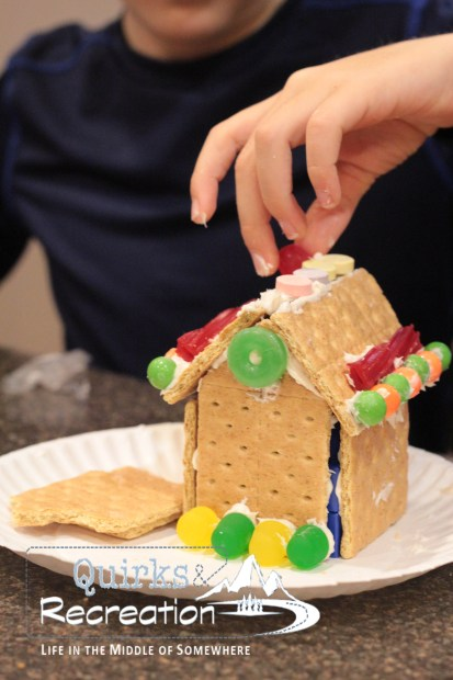 boy decorating a gingerbread house with candy