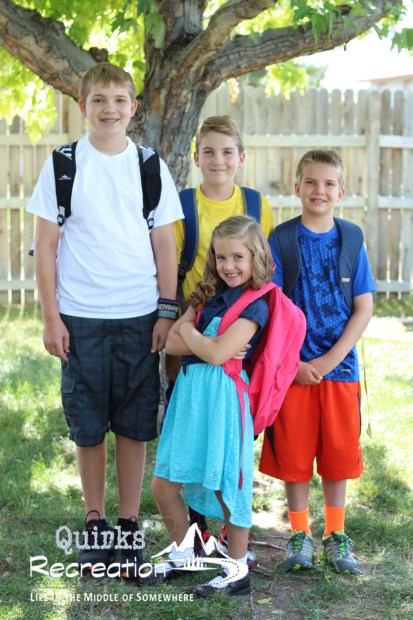 four siblings posing for back to school photo