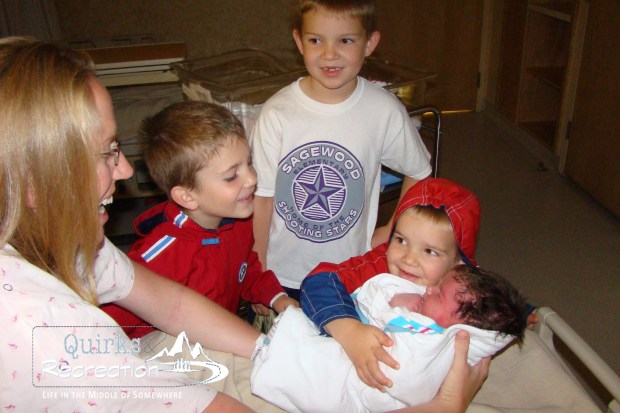 three brothers meeting their baby sister for the first time