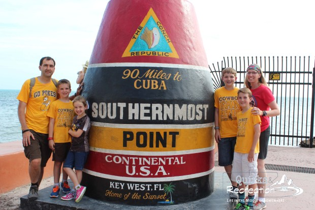family posing at the US southernmost point Key West, Florida