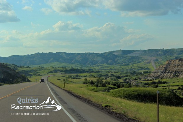 road through Theodore Roosevelt National Park in North Dakota with grassy hills
