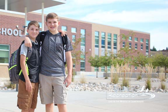 brothers standing in front of a middle school