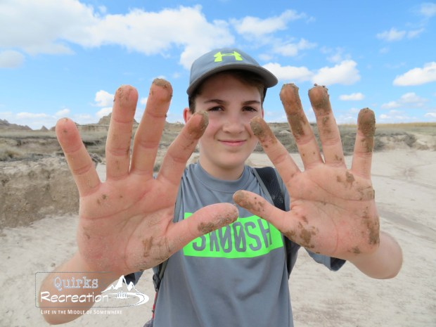 Boy showing muddy hands from hiking Badlands National Park