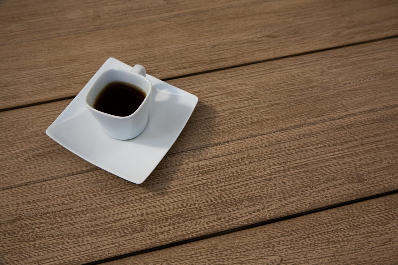 photo of a saucer with a hot beverage on top of a wooden surface