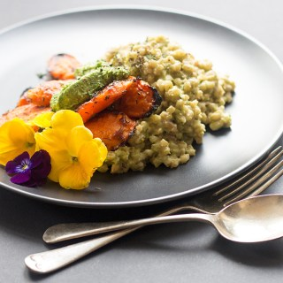 Vegan barley risotto served with maple roasted carrots and kale pesto.