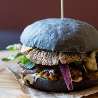 Black burger with crispy oyster mushrooms and spicy eggplant (vegan).