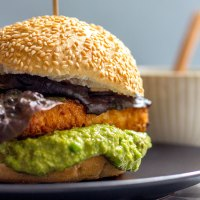 Crispy tofu burger with green pea and caper mayo (vegan).