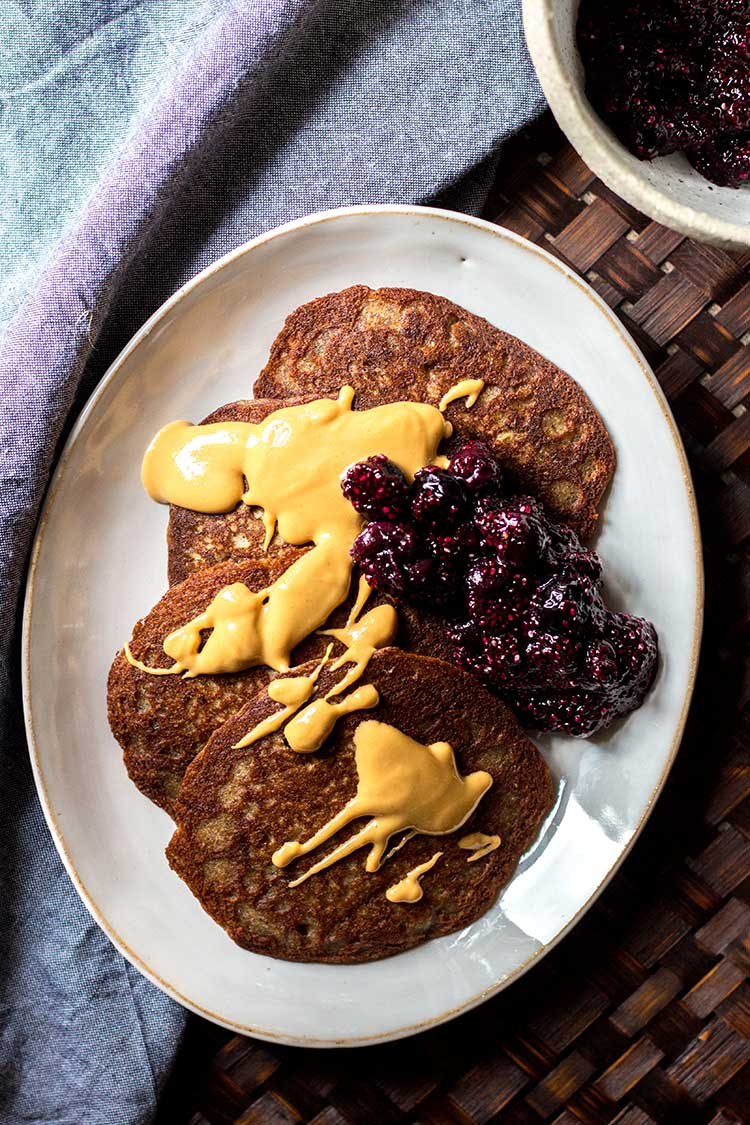 Overhead shot of buckwheat pikelets, drizzled with peanut butter and a spoonful of blueberry chia jam (vegan and gluten free).