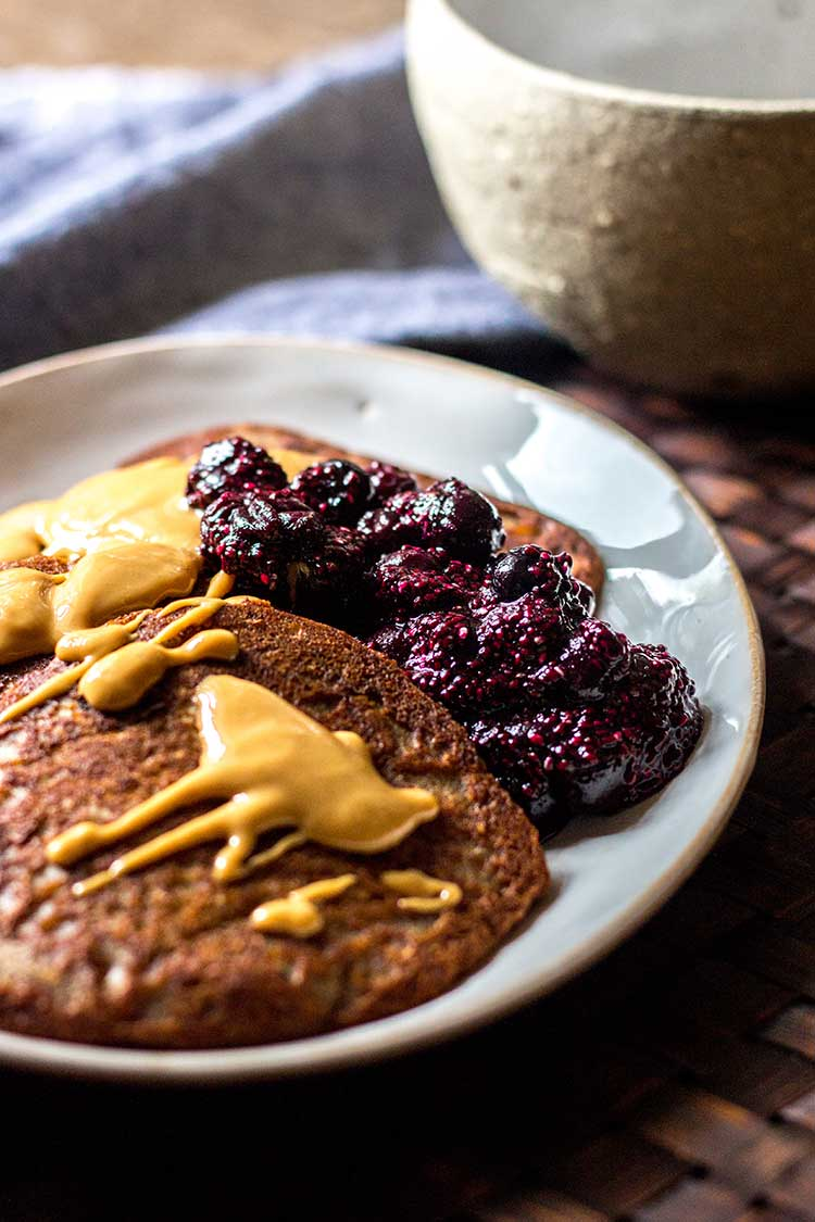 Photo of buckwheat pikelets topped with peanut butter and blueberry chia jam (vegan and gluten free).