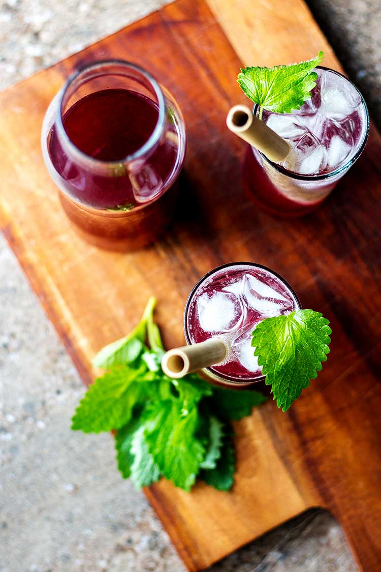 Overhead shot of boysenberry shrubs, mixed with soda water and garnished with a sprig of lemon balm.