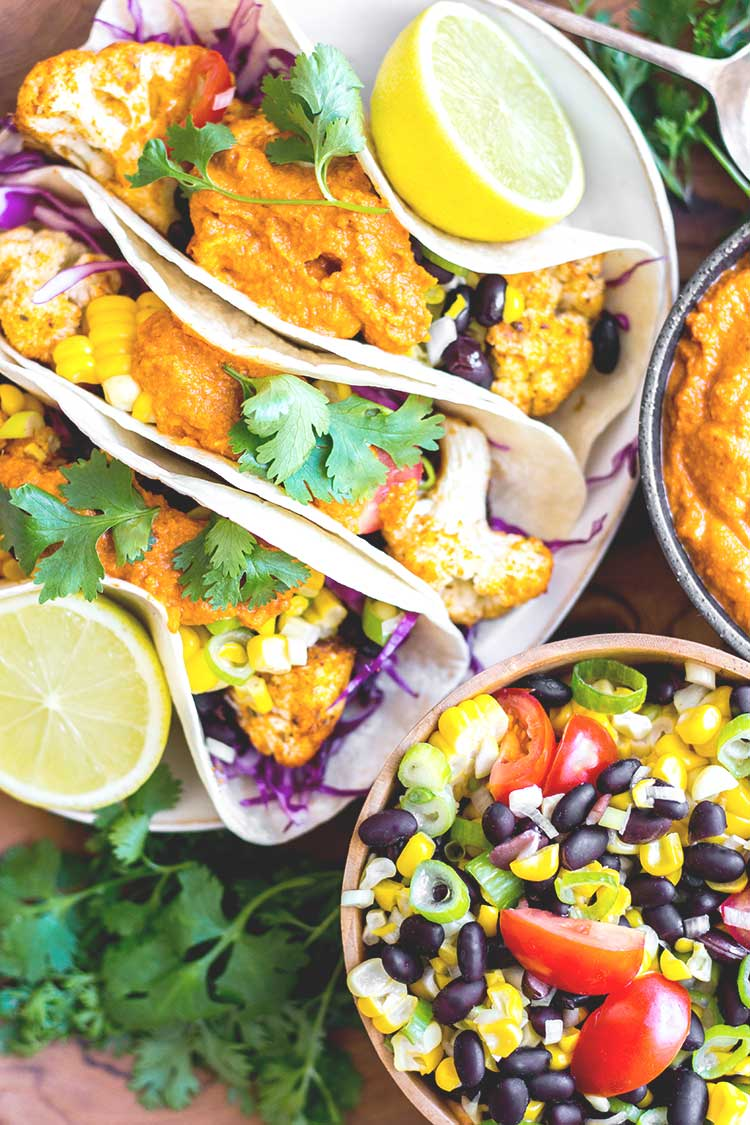 Overhead view of cauliflower tacos ready to serve, with almond chipotle salsa and salad (vegan and gluten free).