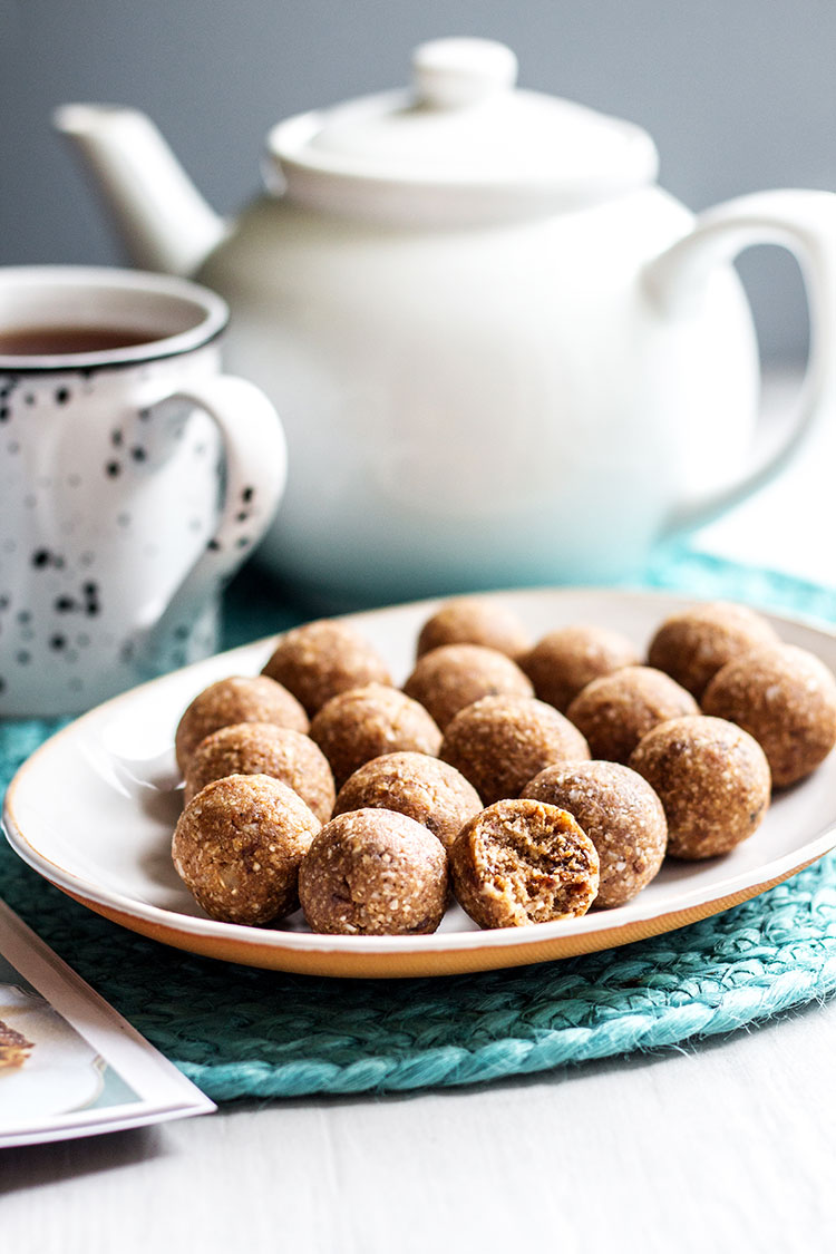 Hot cross bun bliss balls for Easter, pictured with a pot of tea (vegan and gluten free).