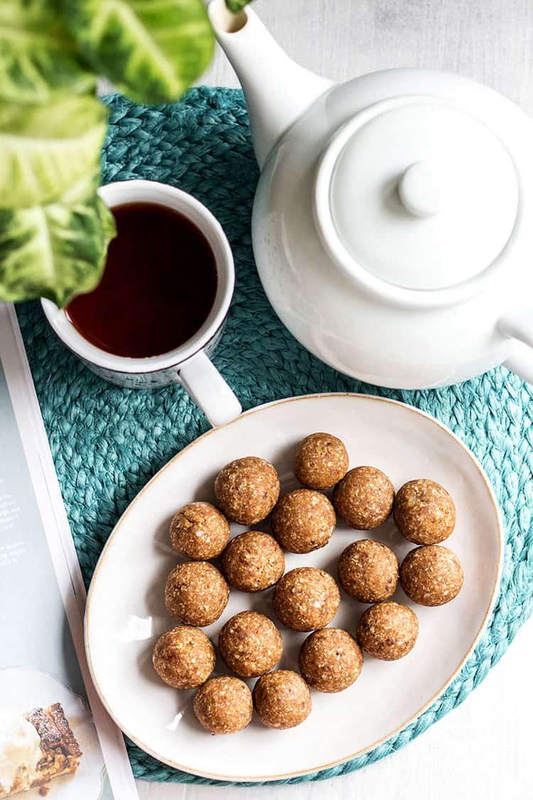 Overhead of hot cross bun flavoured bliss balls, served with a pot of tea.