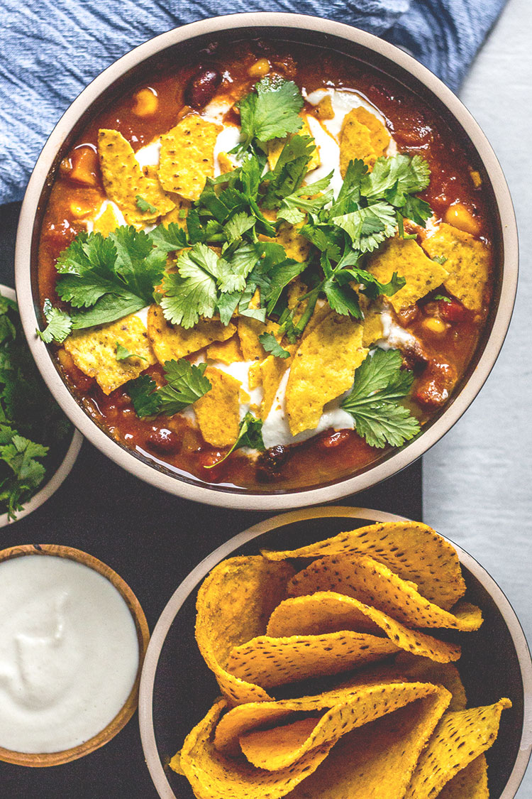 Black bean and corn nacho soup - a Mexican inspired soup topped with corn chips and lime cashew cream. (Vegan and gluten free).