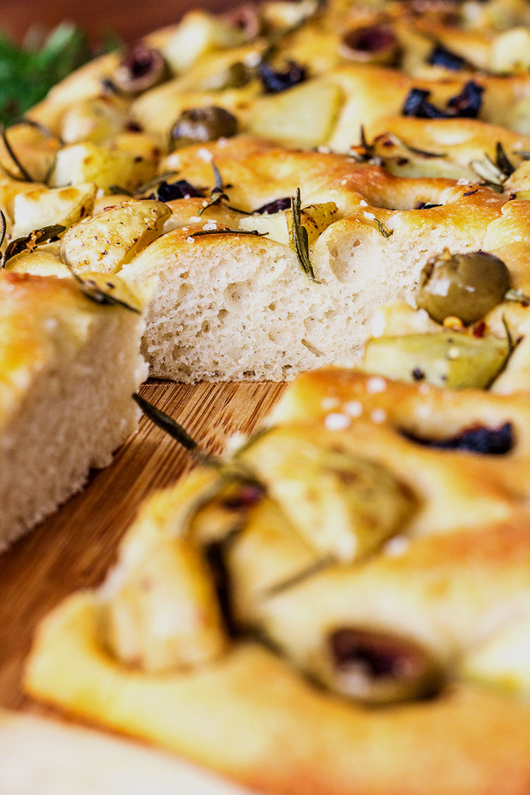 Potato foccacia topped with olives, rosemary and potato, sliced and ready to serve.