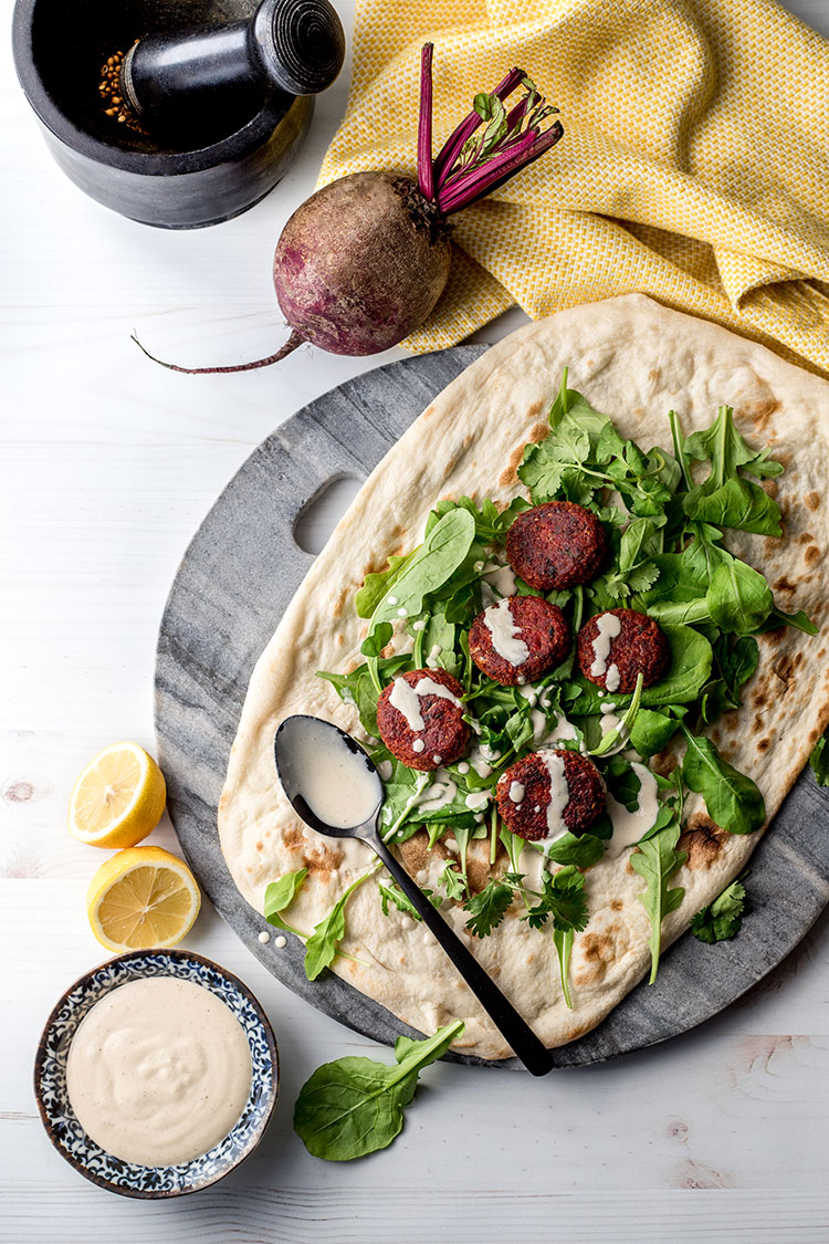 Beetroot falafel, served with flat bread, salad greens and a simple tahini sauce.