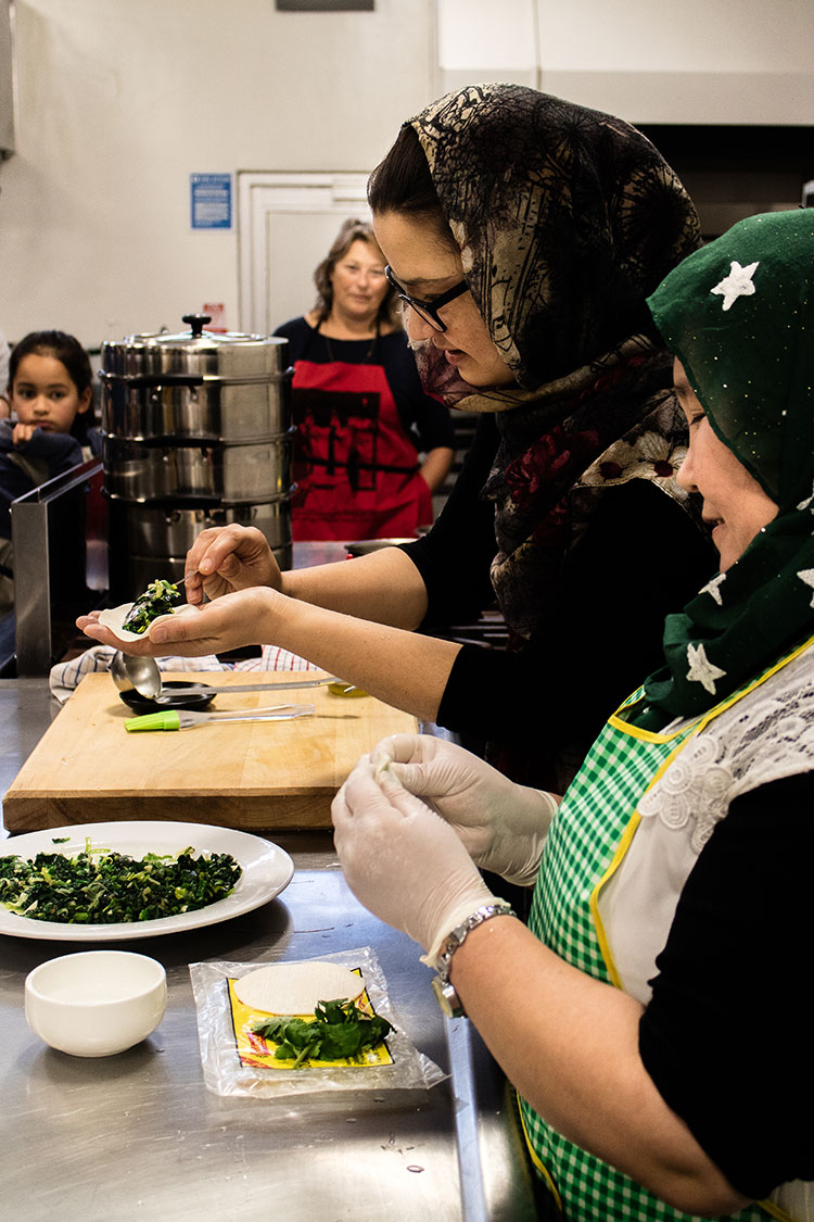 The Home Kitchen team demonstrating how to make ashak - Afghan vegetable dumplings, at a cooking class.