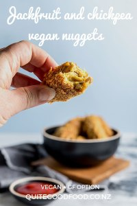 A hand holding a jackfruit and chickpea nugget, with a bite taken from it, showing the moist and textured interior of the nugget. There is a bowl of vegan nuggets and tomato ketchup in the background.