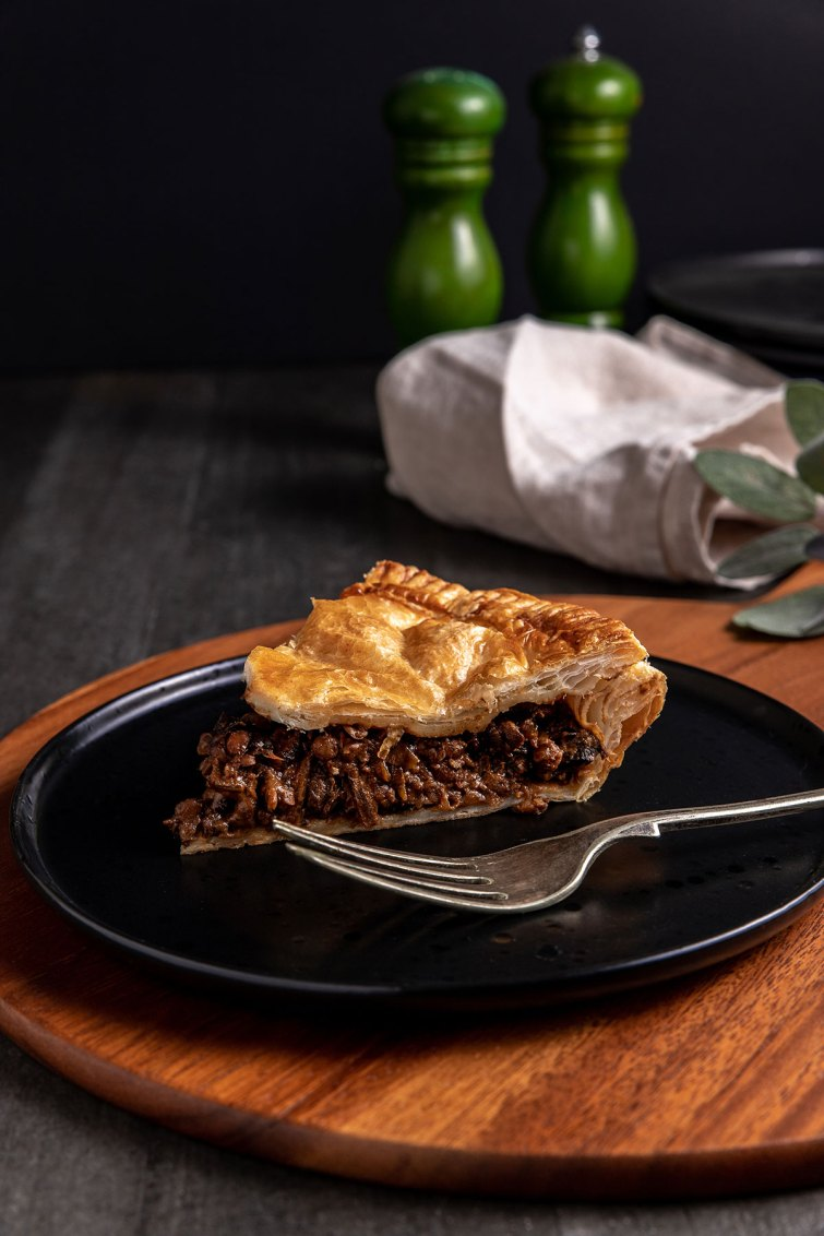 A slice of mushroom, onion and lentil pie sitting on a black plate. The filling is dark and glossy.