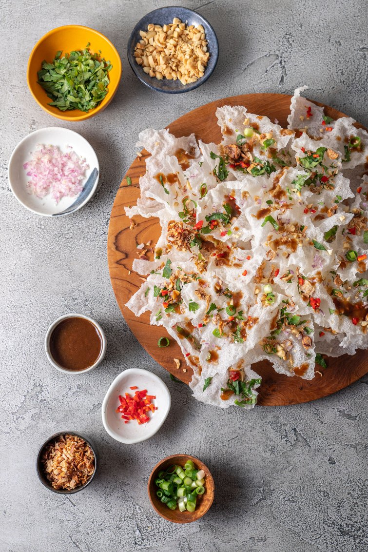 A wooden platter piled high with fried rice paper crisps, scattered with peanut, onion, coriander, shallots, spring onion and chilli.