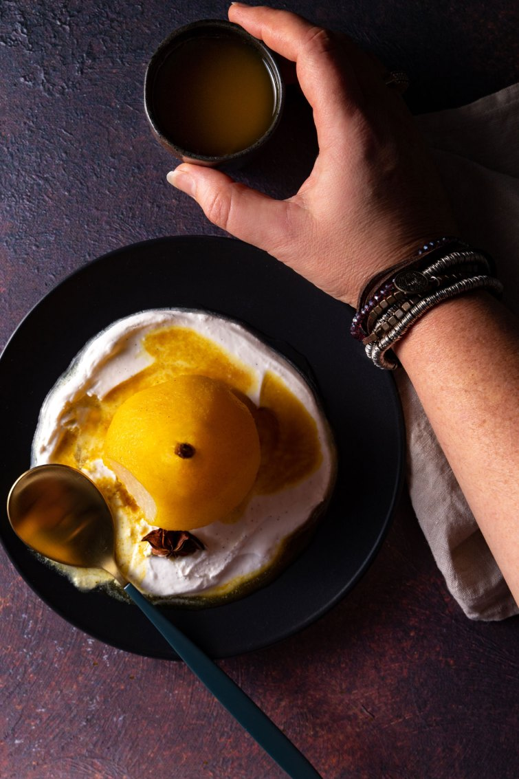 An overhead photo of a golden poached pear on a black plate, with coconut yoghurt, a star anise, a puddle of poaching liquid, and a hand picking up a small container of extra poaching liquid for pouring.
