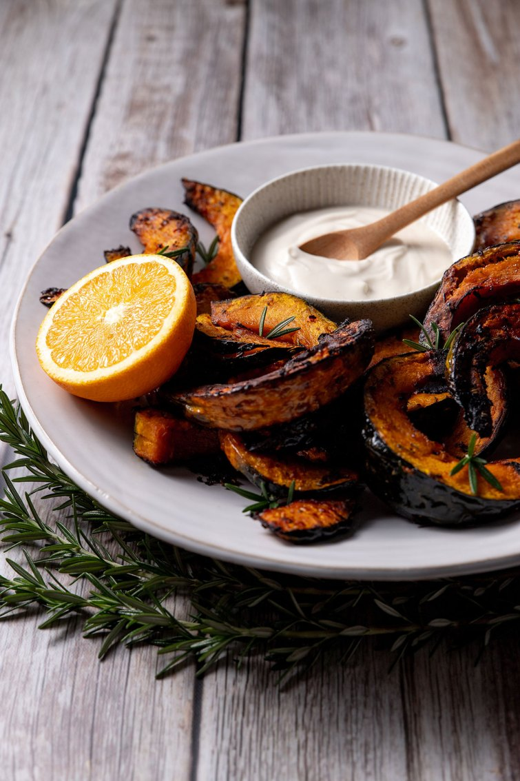A white plate with slices of roast buttercup pumpkin, pictured with a small bowl of coconut yoghurt and tahini sauce, half an orange and a sprig of rosemary.