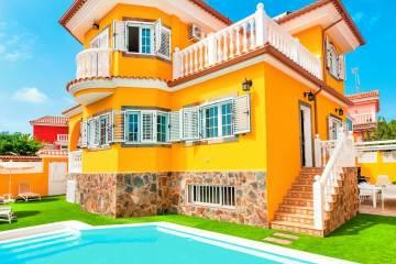 uma casa amarela grande e bonita com piscina e jardim