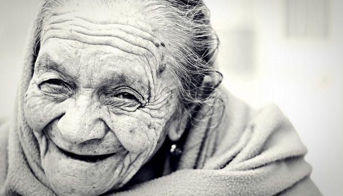 foto preta e branca de uma senhora idosa sorrindo