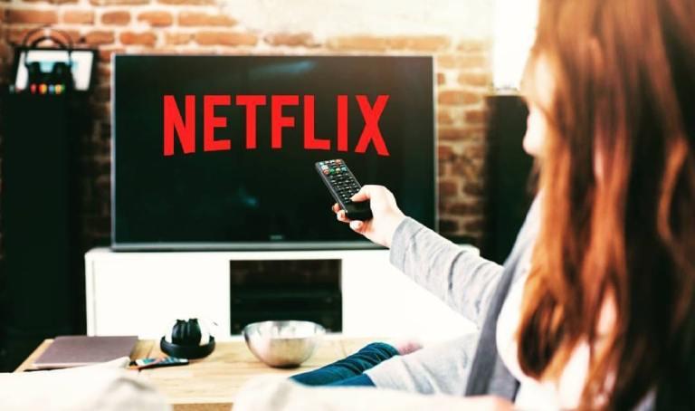 Televisão ligada nos filmes da Netflix - Mulher com controle na mão procurando um filme