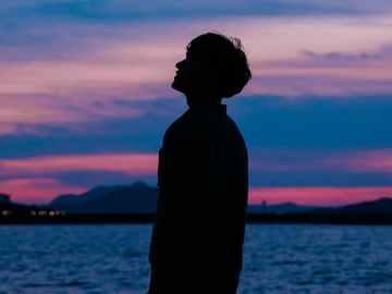 homem orando ao anoitecer ao ar livre