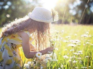 imagem de uma garota feliz em meio a um campo de flores com um chapéu branco