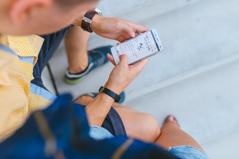 homem sentado mexendo no celular enviando mensagens