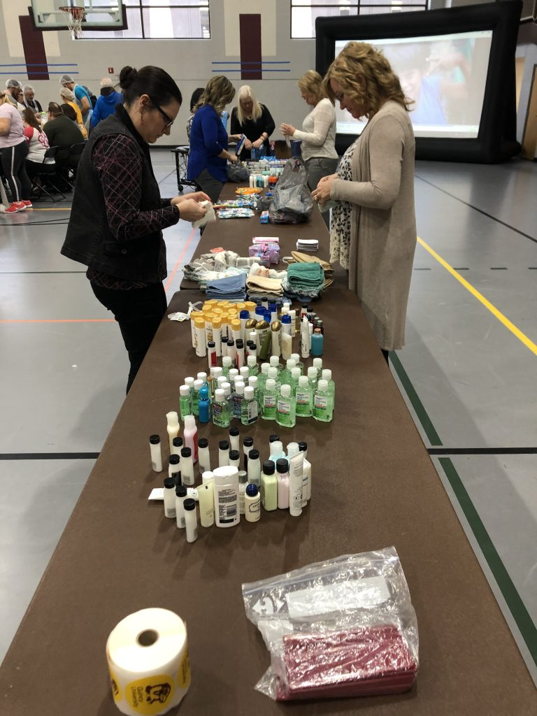 This is a picture of volunteers sorting hygiene products on a table.