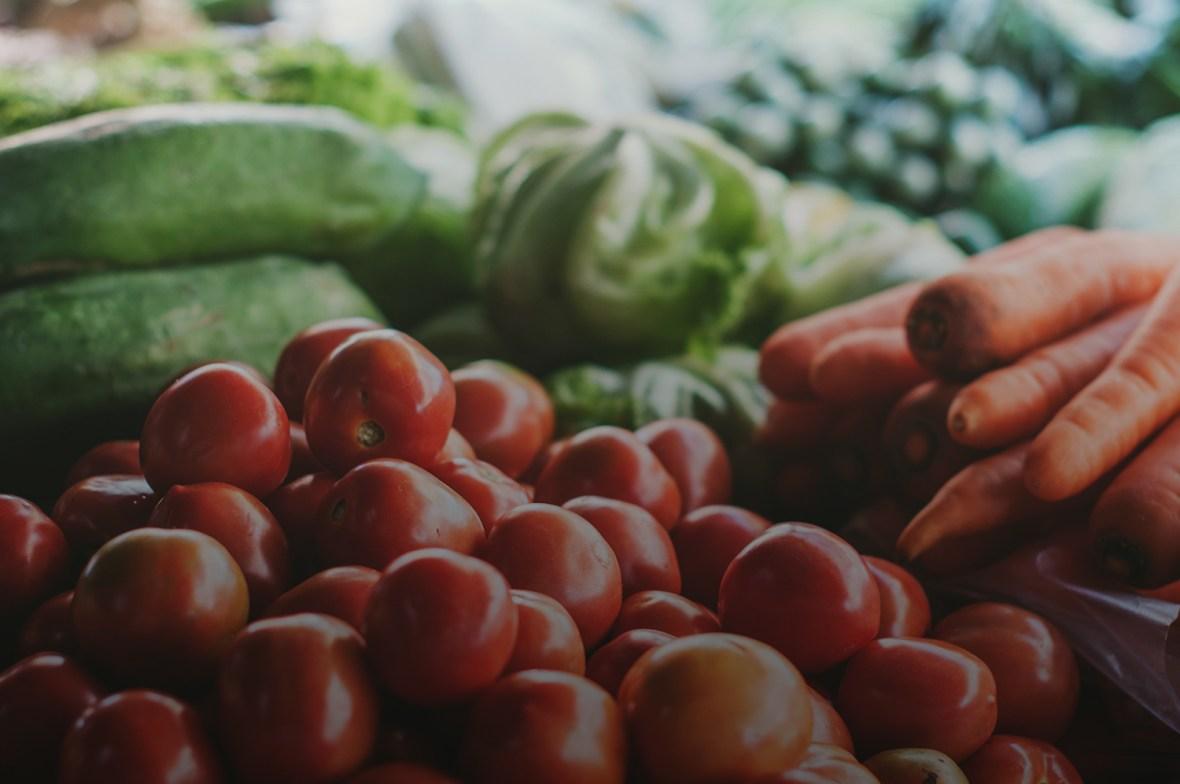 Cà chua đỏ bên cạnh cà rốt cam và rau xanh