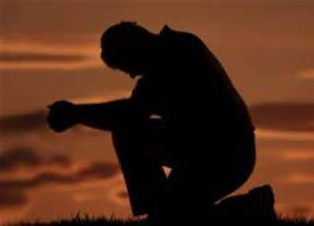Teenager prays in dark setting