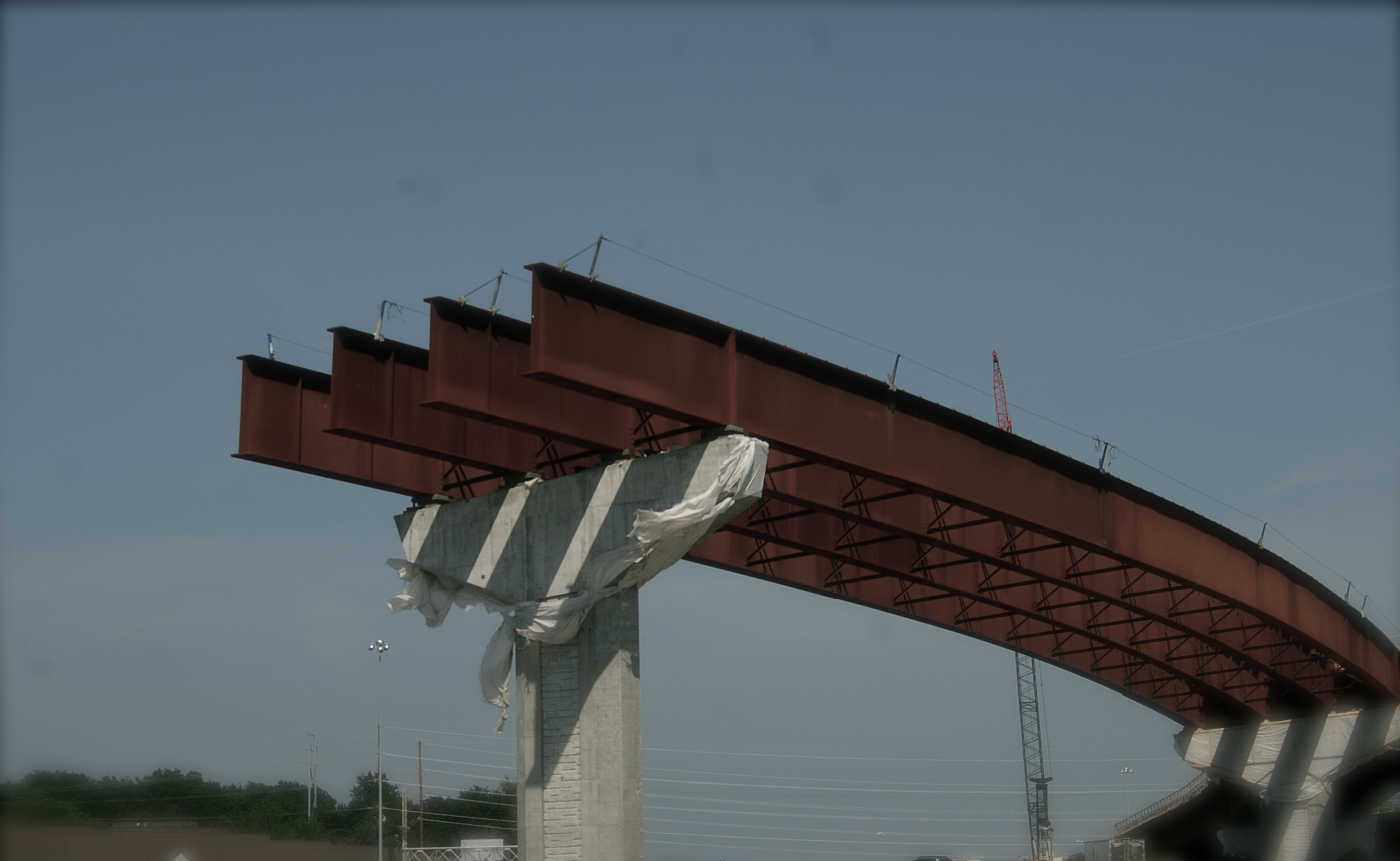 cropped photograph of a highway bridge under construction, showing heavy I-beams looming beyond the column support