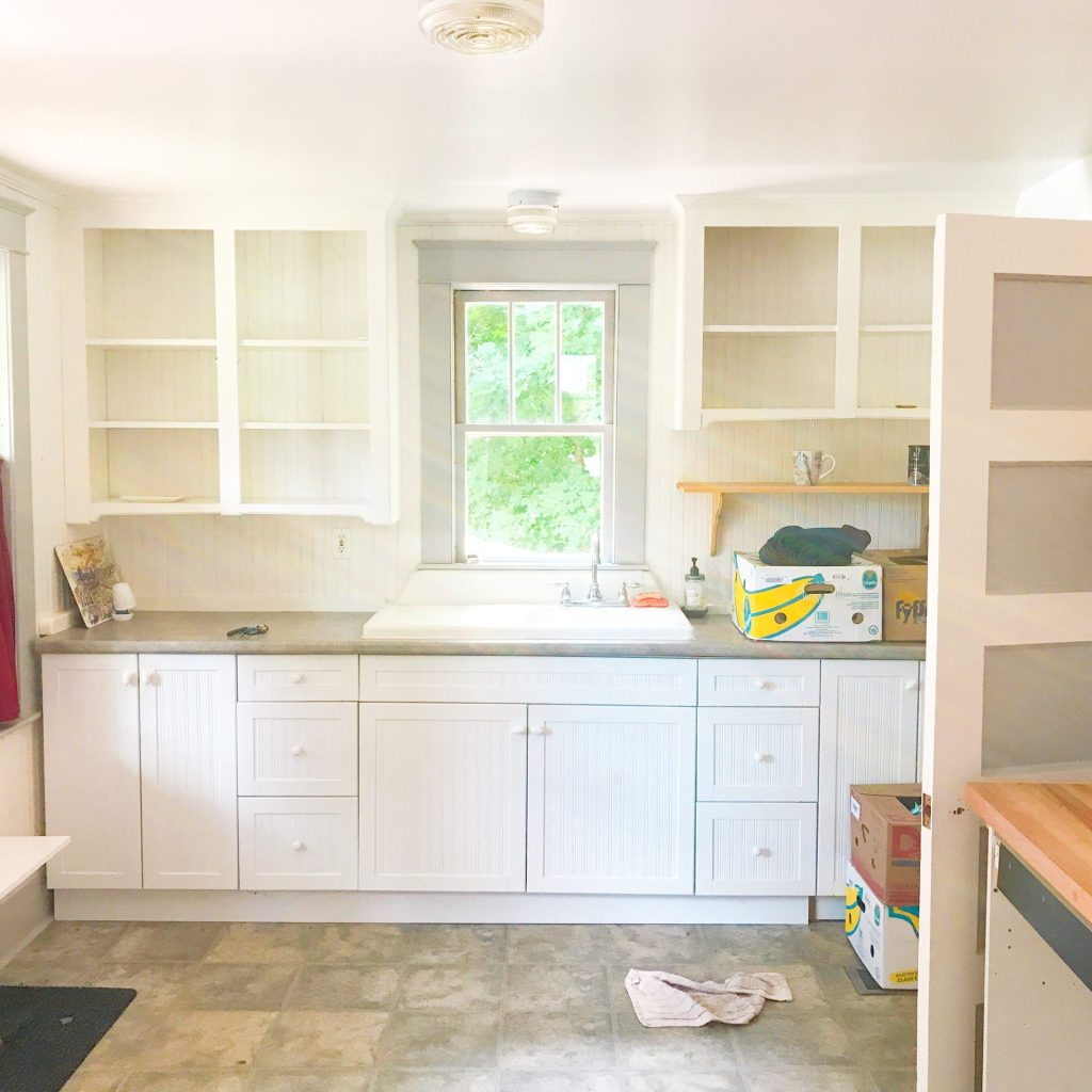 A photo of my kitchen. It's white and has a beautiful, original farmhouse sink.