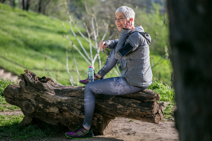 Athletic elderly woman resting during her run at an Elk Grove area park