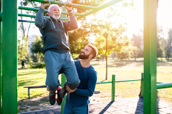 Alexandria son helps his father do a pull up at a park