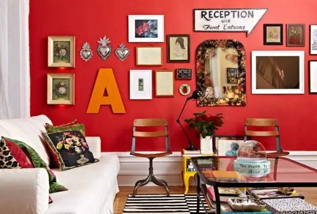 Lembranças vintage e pinturas modernas em uma sala vermelha brilhante de um estilo boêmio