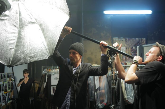 Alex Antitch adjusts a strobe with his assistant